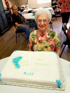 """This picture shows a mature woman with short white hair and eyeglasses is wearing a pink and green floral print shirt. She smiles as she sits in front of her birthday cake. The cake has fancy white icing with baby blue flowers and mint green-colored leaves. The light green text on the cake says, """"Wow 103 Years Young"""" inside a heart design. Below that, the word """"Ruby"""" is written in baby blue colored icing. A man in a black shirt sits behind the mature woman, looking on as she poses for the picture. Other people are at the edges of the image."""